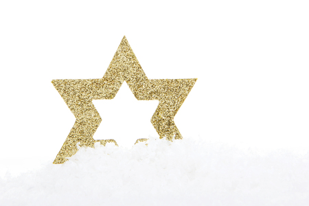 christmas, golden christmas star on artificial snow with white background