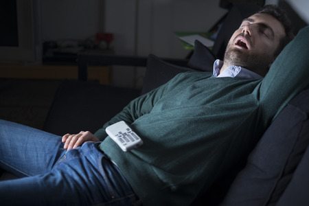 Photo for Man sleeping and snoring in front of television on the couch - Royalty Free Image