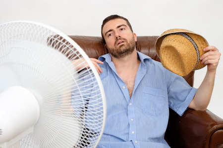 Photo for Flushed man feeling hot in front of a fan - Royalty Free Image