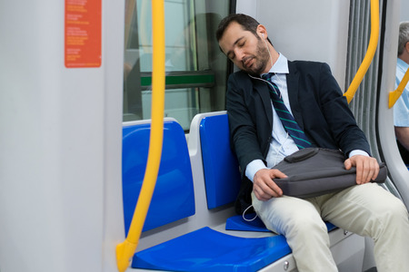 Tired businessman sleeping on the underground metro