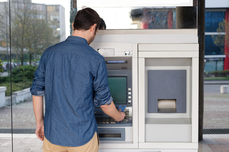 Photo pour Man using his credit card in an atm for cash withdrawal - image libre de droit