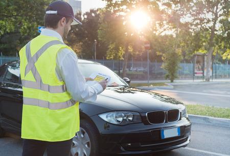 Photo pour Police officer giving a ticket fine for parking violation - image libre de droit
