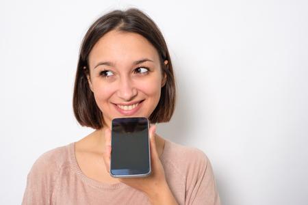 Photo pour Young woman using phone vocal assistant and sending vocal message - image libre de droit