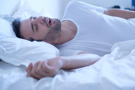 Photo pour Man snoring because of sleep apnea sahs syndrome lying in the bed - image libre de droit
