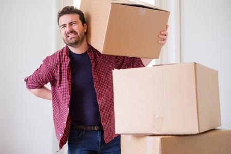 Foto de Man moving boxes and feeling back pain because heavy weight - Imagen libre de derechos