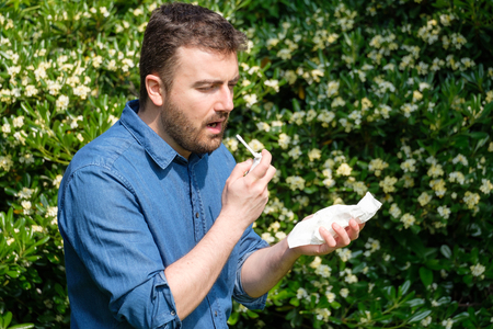 One man in blue shirt with allergy or cold, blowing his nose with tissue outside green trees background. Flu season, vaccination.