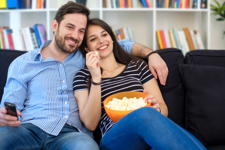 Photo pour Young couple watching tv at home and having fun - image libre de droit