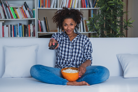 Photo pour Happy woman sitting at home with remote control watching tv - image libre de droit