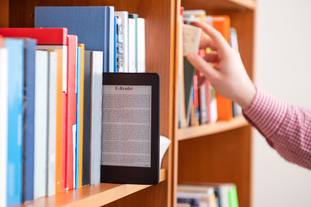 Photo for Hand of student keeping digital tablet in bookshelf in school library - Royalty Free Image