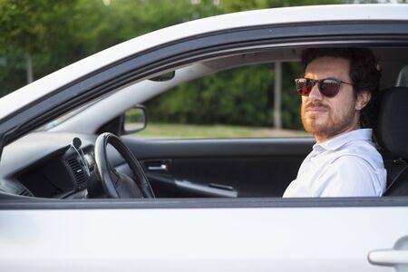 Photo pour Cheerful man portrait sitting in his car - image libre de droit