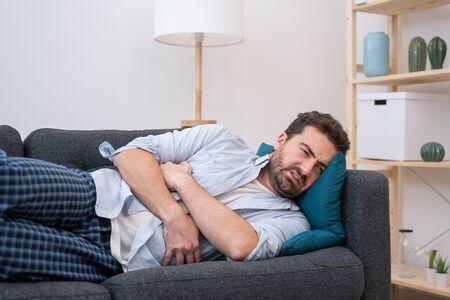 Photo pour Man portrait suffering stomach ache at home - image libre de droit