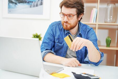 Photo pour Worried man sitting in home office and using credit card - image libre de droit