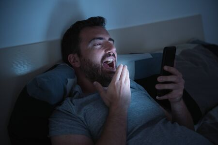 Photo pour Man in bed watching smartphone display - image libre de droit
