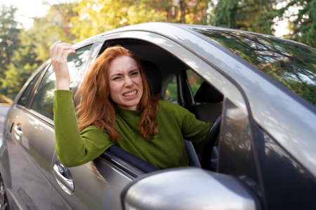 Photo pour Frustrated woman driving her car and gesturing roughly - image libre de droit