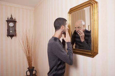 Foto de young man looking at an older himself in the mirror - Imagen libre de derechos