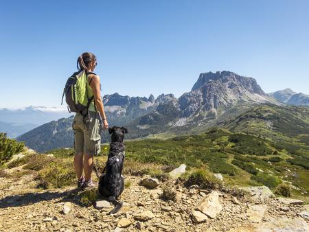 Foto de young beautiful woman enjoying the view with her dog during hiking trip in the mountain - Imagen libre de derechos