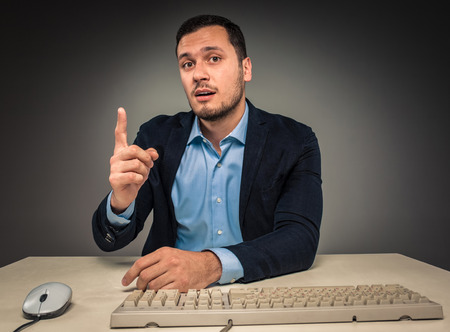 Foto de Handsome man raised his index finger and looking at the camera, sitting at a desk near a computer, isolated on gray background. Concept of the idea or warning - Imagen libre de derechos