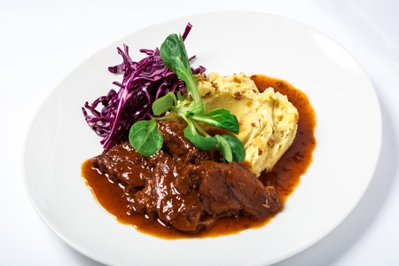 Cooked veal cheeks in gravy with potatoes and cabbage, decorated fresh herbs in white plate. Close-up