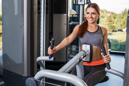 Muscular young brunette doing exercises on the simulator in the gym. She is wearing a gray tracksuit