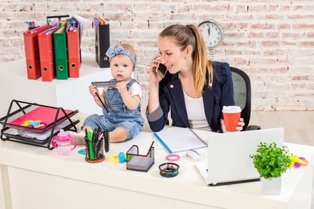 Photo for Family Business - telecommute Businesswoman and mother with kid is making a phone call - Royalty Free Image
