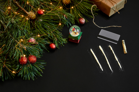 Cocaine divided into paths with Xmas toys and spruce branch on black background top view.