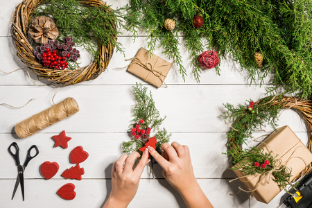 Foto de Christmas handmade diy background. Making craft xmas wreath and ornaments. Top view of white wooden table with female hands. - Imagen libre de derechos