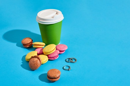 Hot coffee in green paper cup with white lid and macaroons on bl