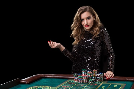 Photo pour Woman playing in casino. Woman stakes piles of chips playing roulette - image libre de droit