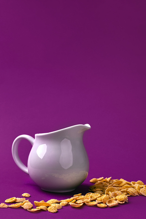 Close-up view of jug with milk and crunchy corn flakes on purple background