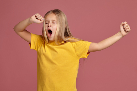 Photo for little girl in a yellow t-shirt. stretches and yawns - Royalty Free Image