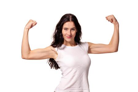Foto de Happy young woman shows her muscles isolated on white background - Imagen libre de derechos