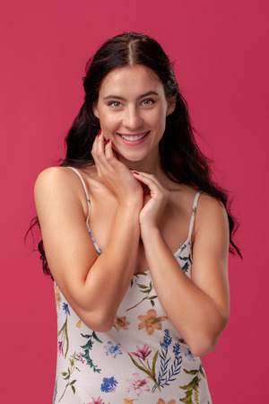 Photo pour Portrait of a pretty young woman in a light dress standing on pink background in studio. People sincere emotions. - image libre de droit