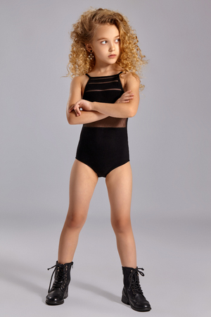 Foto de Beautiful little girl gymnast in a black sports swimsuit and boots on a gray background. - Imagen libre de derechos