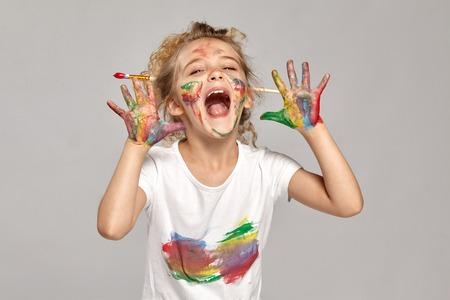 Foto de Beautiful little girl with a painted hands and cheeks is posing on a gray - Imagen libre de derechos