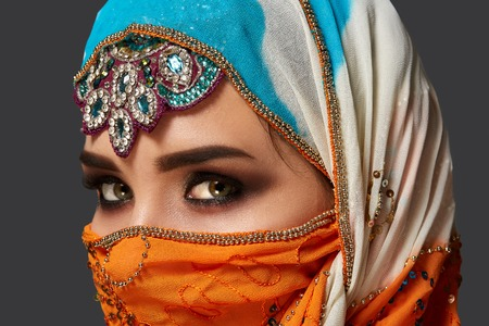 Photo pour Studio shot of a chrming female wearing the colorful hijab decorated with sequins and jewelry. Arabic style. - image libre de droit