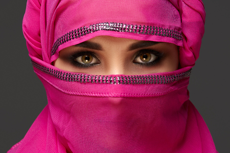Photo pour Close-up shot of a young charming woman wearing the pink hijab decorated with sequins. Arabic style. - image libre de droit
