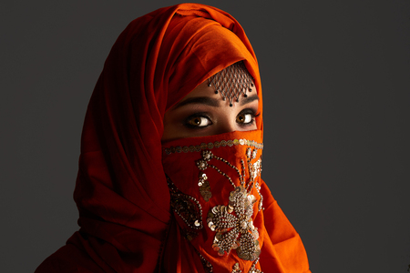 Photo pour Studio shot of a young charming woman wearing the terracotta hijab decorated with sequins and jewelry. Arabic style. - image libre de droit