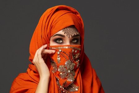Photo pour Close-up portrait of a good-looking young woman with beautiful smoky eyes and fine jewelry on the forehead, wearing the terracotta hijab decorated with sequins. She is posing sideways and looking at the camera on a dark background. Human emotions, facial expression concept. Trendy colors. Arabic style. - image libre de droit