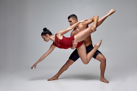 Photo for The couple of an athletic modern ballet dancers are posing against a gray studio background. - Royalty Free Image