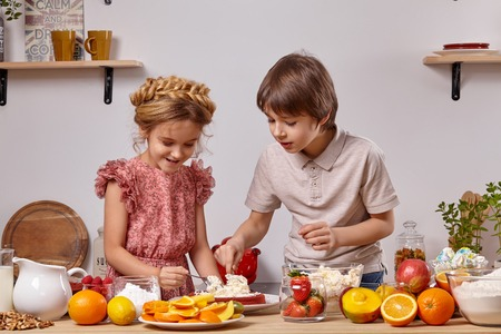 Photo pour Little friends are making a cake together at a kitchen against a white wall with shelves on it. - image libre de droit