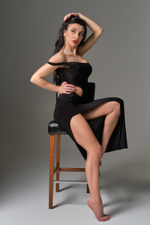 Photo pour Young attractive brunette sexy woman sits on chair in erotic black cocktail dress. Gray background - image libre de droit