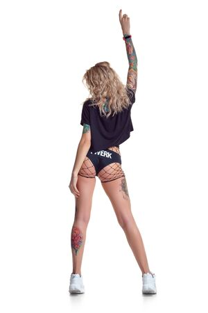 Foto für Beautiful blonde dancer woman in booty shorts and fishnet stand backwards isolated on white background - Lizenzfreies Bild