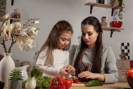 Photo for Mother and her daughter are making a vegetable salad and having fun at the kitchen. - Royalty Free Image