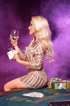 Photo pour Blonde woman with a perfect hairstyle and bright make-up is posing with playing cards in her hands. Casino, poker. - image libre de droit