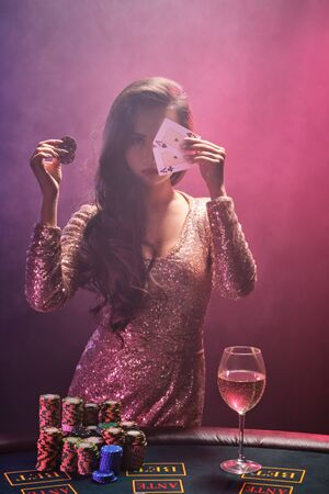 Photo pour Brunette girl with a perfect hairstyle and bright make-up is posing with playing cards and gambling chips in her hands. Casino, poker. - image libre de droit