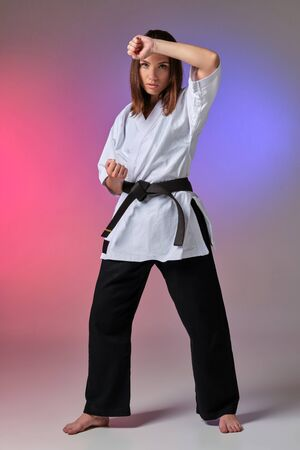Photo pour Athletic woman in traditional kimono is practicing karate in studio. - image libre de droit