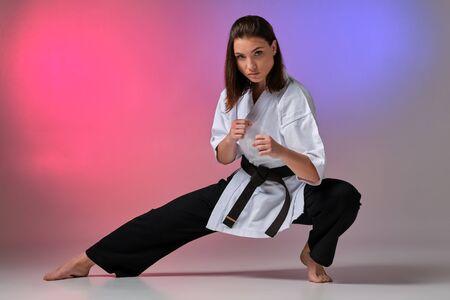 Foto de Athletic woman in traditional kimono is practicing karate in studio. - Imagen libre de derechos