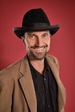 Photo pour Middle-aged man with beard and mustache, wears black hat and brown jacket posing against a red background. Sincere emotions concept. - image libre de droit