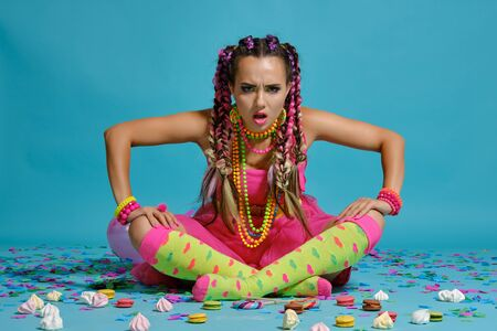 Photo pour Lovely girl with a multi-colored braids hairstyle and bright make-up, posing in studio with air balloons and confetti against a blue background. - image libre de droit