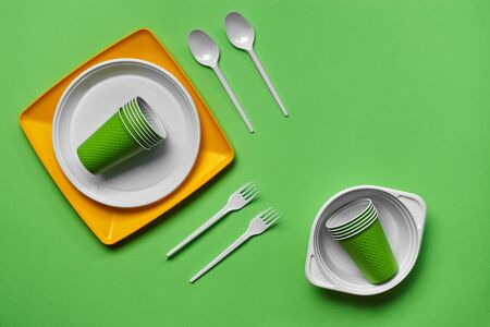 Photo pour Colorful plastic disposable tableware, such as two plates, spoons, forks, folded cups and one bowl on green background with copy space. The concept of picnic utensil. Also used in fast food restaurants, takeaways. Top view. Selective focus. Close-up shot. - image libre de droit
